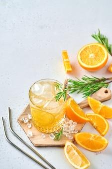 Jus d'orange ou cocktail au romarin et à l'orange avec de la glace en verre, limonade d'été froide sur fond d'ardoise gris clair, de pierre ou de béton. concept de plage avec une ombre solaire profonde. vue de dessus.