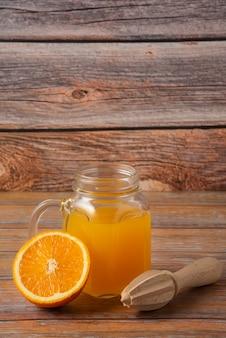 Jus d'orange dans un bocal en verre sur la table en bois