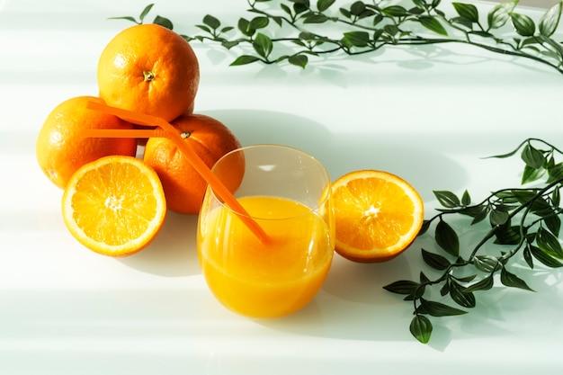 Jus d'orange dans un verre entouré d'oranges naturelles et de quelques feuilles vertes avec un fond blanc lumière du soleil naturel
