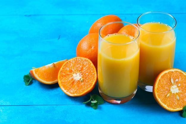 Jus d'orange dans des verres et des oranges