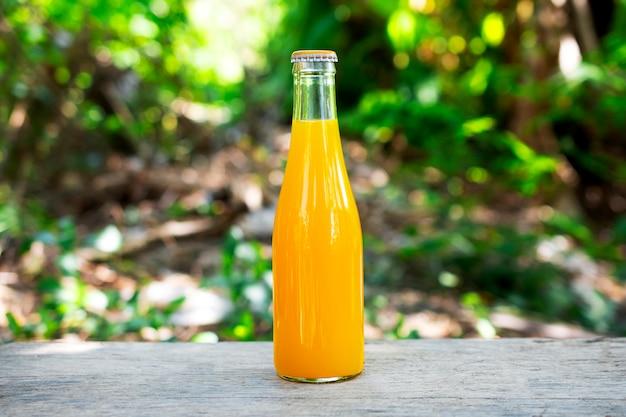 Jus d'orange emballé dans des bouteilles en verre plateau en bois et fond de nature verdoyante