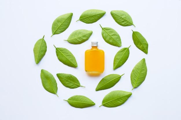 Jus d'orange avec des feuilles vertes sur fond blanc.