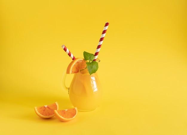 Jus d'orange fraîchement pressé dans une tasse en verre stylisée comme une cruche, des tranches d'orange rouge, des feuilles de menthe fraîche et des tubes de carton rouges contrastants. vitamines naturelles. concept d'alimentation saine. la prévention des maladies.