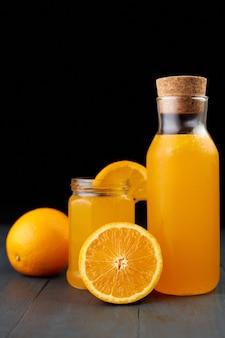 Jus d'orange frais dans un bocal en verre et bouteille avec des fruits frais sur table en bois, fond noir