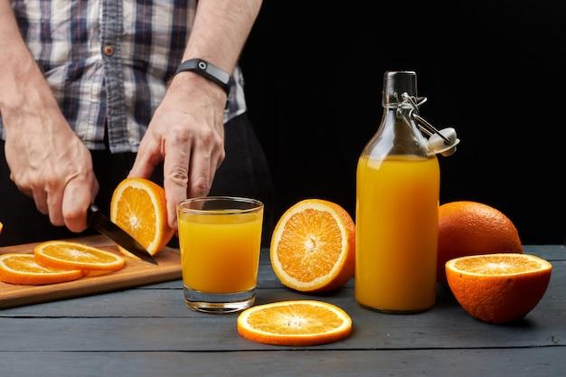 Jus d'orange frais dans un verre et une bouteille avec des fruits frais tranchés avec un couteau. l'homme coupe les oranges à la table en bois sur fond noir