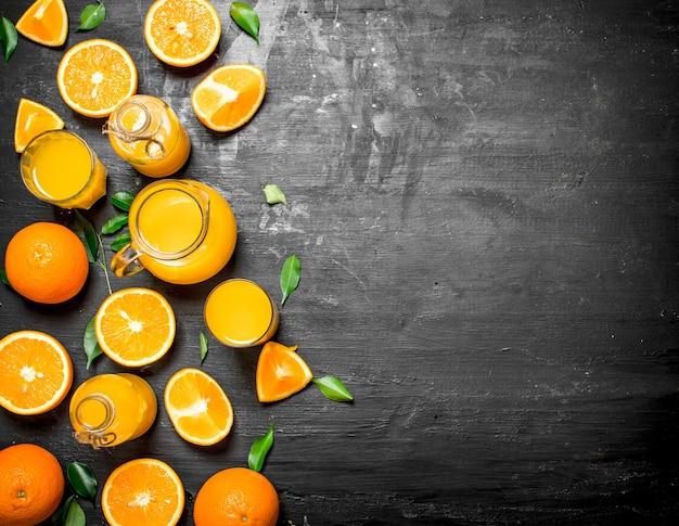 Jus d'orange frais avec des feuilles sur un tableau noir.