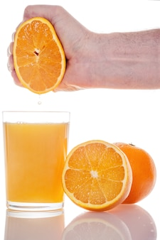 Jus d'orange frais pressé à la main dans un verre isolé sur mur blanc