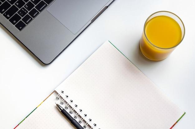 Jus d'orange sur le lieu de travail. ordinateur portable, verre de jus d'orange et cahier sur le bureau blanc.