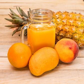 Jus d'orange, mangues et ananas sur une table en bois