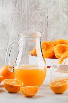 Jus d'orange avec des oranges, presse-agrumes dans une cruche sur une surface blanche
