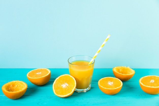 Jus d'orange avec de la paille sur la table bleue