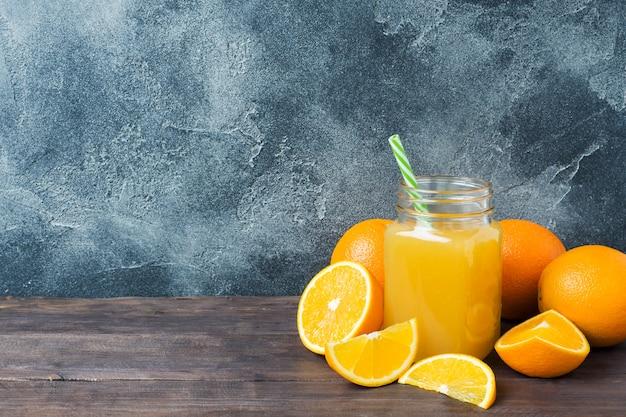 Jus d'orange en pot de verre et oranges de fruits frais sur fond sombre avec espace de copie.