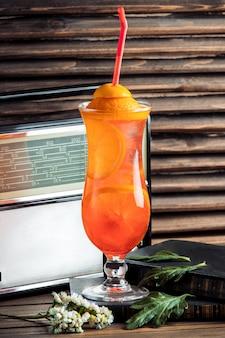 Jus d'orange avec des tranches dans un verre avec un tuyau.