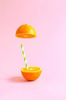 Jus d'orange avec tubule. orange coupé en deux sur fond rose pastel.