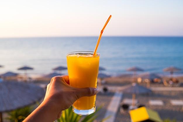 Jus d'orange en verre. boisson froide. main avec du jus de fruits frais et délicieux d'oranges mûres