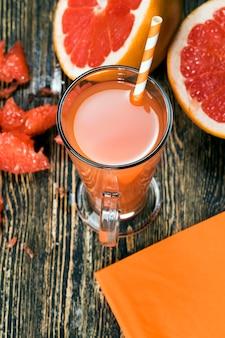 Jus de pamplemousse frais à base de pamplemousses rouges juteux de manière naturelle, à côté de fruits frais