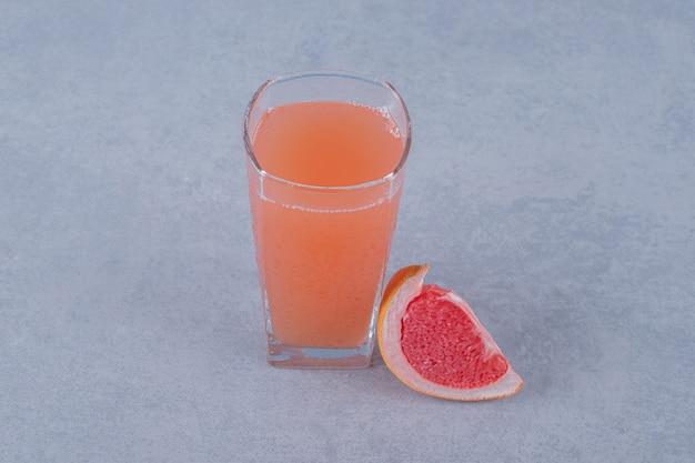 Jus de pamplemousse frais et tranche de fruit sur une surface grise