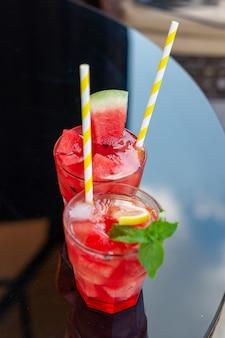 Jus de pastèque frais avec menthe et glace dans le verre sur table en verre. dessert d'été sucré, concept d'aliments sains de cocktail, gros plan. heure d'été. mise au point sélective.