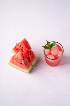 Jus de pastèque froide fraîche avec des glaçons et des feuilles de menthe verte dans une boisson en verre près de deux tranches de pastèque sur blanc selective focus
