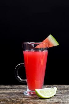 Le jus de pastèque sucré de pastèques et de morceaux de citron vert ou de jus de citron rouge est un produit naturel sain et diététique jus de pastèque avec de la lime aigre