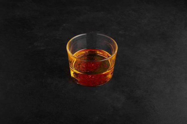Jus de poire dans une tasse en verre sur une surface noire.