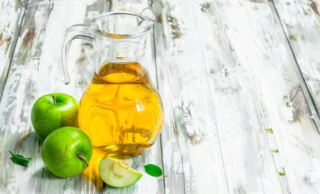 Jus de pomme dans un bocal en verre avec des pommes. sur un fond en bois blanc.