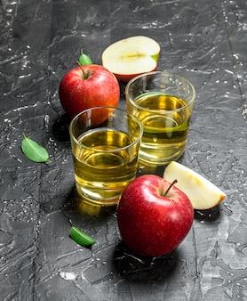 Jus de pomme dans un bocal en verre avec des pommes fraîches dans une boîte.