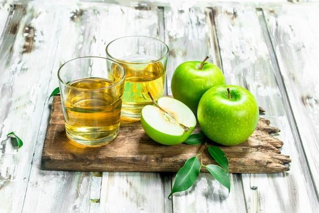Jus de pomme dans une tasse en verre sur une planche en bois. sur une table en bois blanche.