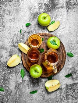 Jus de pomme en pichet sur le plateau avec une pomme verte fraîche