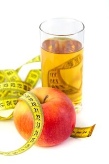 Jus de pomme et de pomme avec ruban à mesurer sur fond blanc, nourriture saine