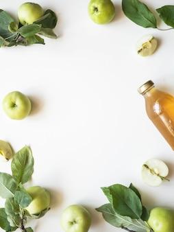 Jus de pomme et pommes fraîches et feuilles sur fond blanc. mise à plat. vue de dessus. copier l'espace