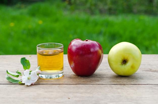 Jus de pomme et pommes sur une table en bois avec une nappe grise sur de l'herbe verte