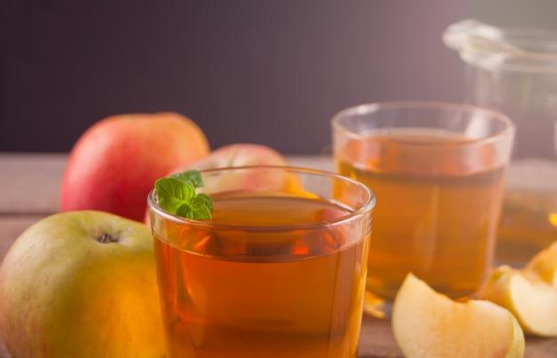 Jus de pomme et pommes sur une table en bois.