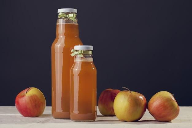 Jus de pomme utile avec des pommes autour d'une table en bois