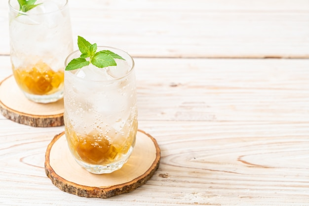 Jus de prune glacé avec soda et menthe poivrée sur table en bois - boisson rafraîchissante