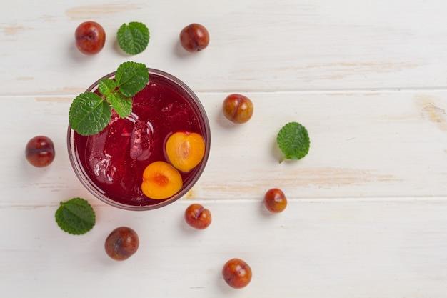 Jus de prunes frais sur la surface en bois blanche.
