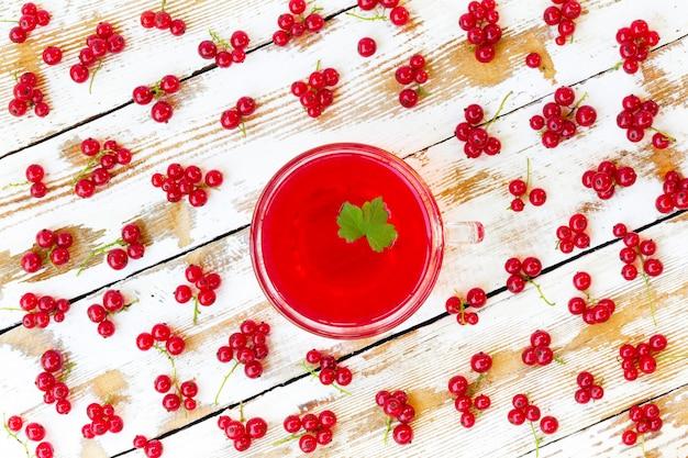 Jus rouge fraîchement pressé avec des feuilles de cassis et des grappes de groseilles sur une table en bois blanche avec des peintures anciennes.