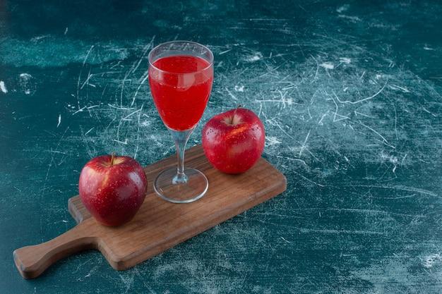 Jus rouge et pomme au tableau, sur la table bleue.