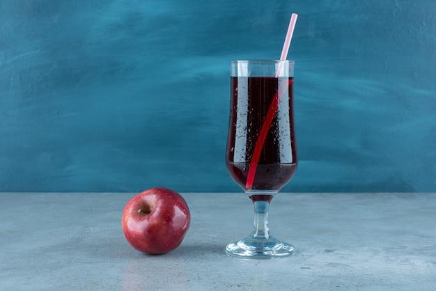 Jus savoureux rouge avec pomme fraîche et paille.
