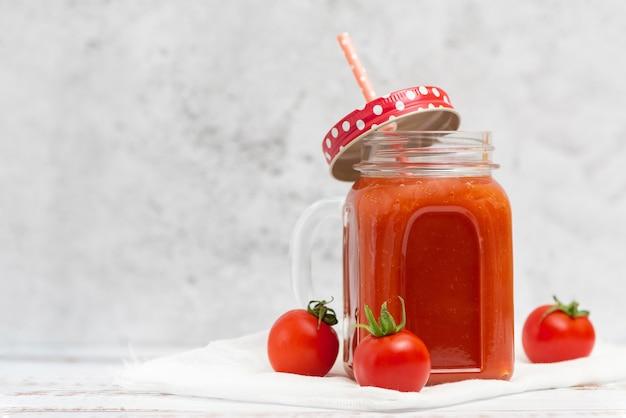 Jus de tomate fraîche en pot et tomates cerises à la lumière.