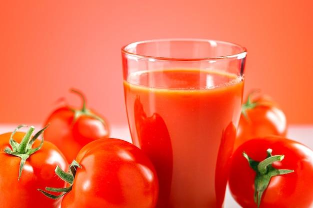 Jus de tomate en verre avec des tomates fraîches sur la table.