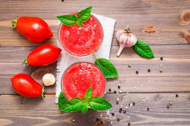 Jus de tomates fraîches appétissant au basilic laisse dans des verres et ingrédients pour sa préparation sur une table en bois. vue de dessus