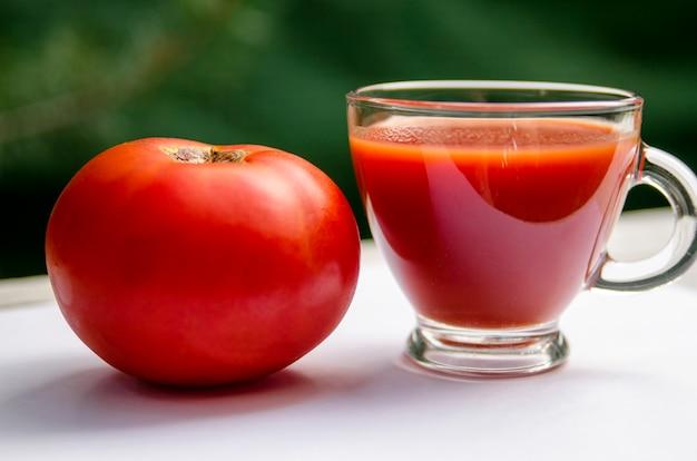 Jus de tomates fraîches dans une coupe en verre et fruits de la tomate, gros plan