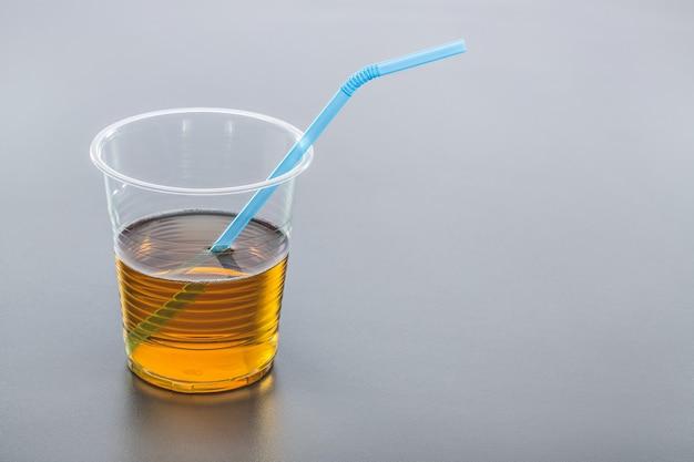 Jus de verre en plastique avec de la paille, sur fond gris. copiez l'espace.