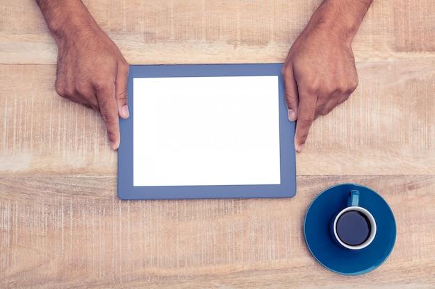 Juste au-dessus du coup de la main qui tient sur une tablette numérique au-dessus d'une table devant un café