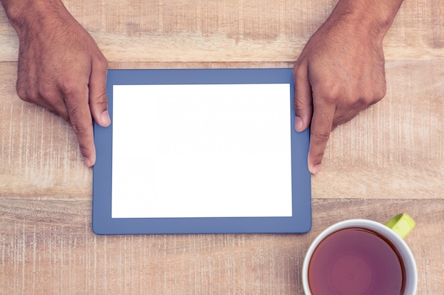 Juste au-dessus d'un homme tenant une tablette numérique au-dessus d'une table devant un café