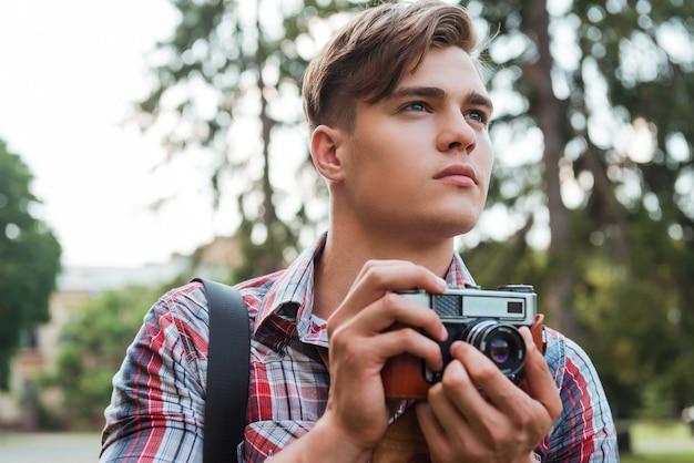 Juste inspiré. beau jeune homme tenant un appareil photo numérique et regardant loin en se tenant debout à l'extérieur