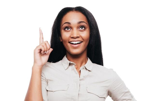 Juste inspiré. heureuse jeune femme africaine pointant vers le haut et souriant en se tenant debout sur fond blanc
