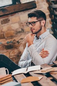 Juste un instant pour réfléchir. vue latérale d'un beau jeune homme réfléchi tenant la main sur le menton et regardant ailleurs alors qu'il était assis sur son lieu de travail