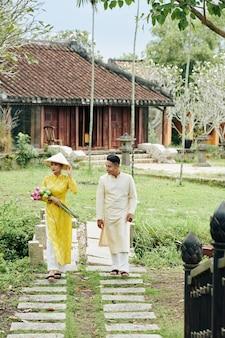 Juste marié beau couple vietnamien en robes traditionnelles marchant dans le jardin après la cérémonie de mariage